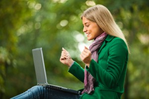 Happy woman using laptop in park